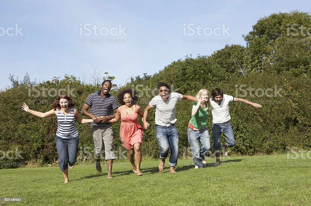 Group portrait of friends running outdoors royalty free stockfoto