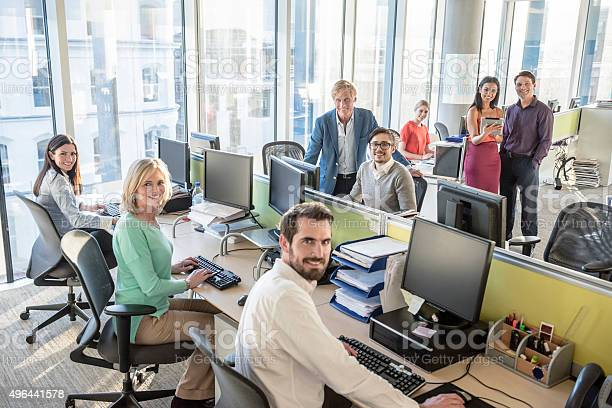 Group Portrait Of Office Workers At Desks In Modern Office Stock Photo - Download Image Now