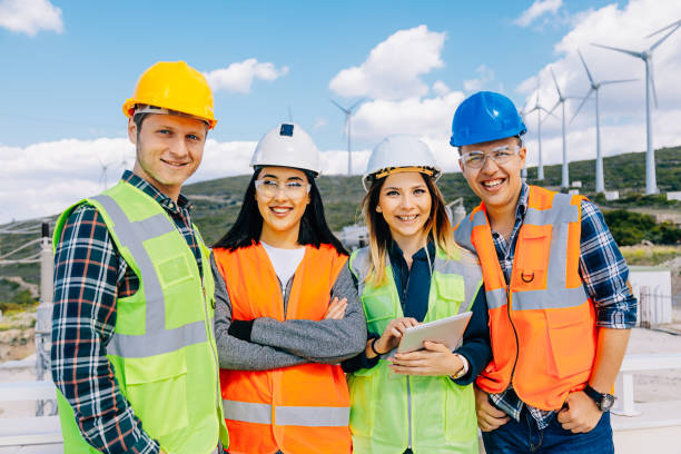 Group portrait of power generation station workers in a windmill farm stock photo