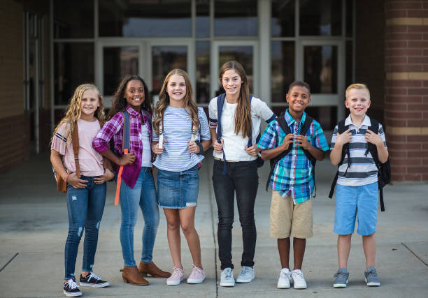 Group portrait of pre-adolescent school kids smiling in front of the school building stock photo