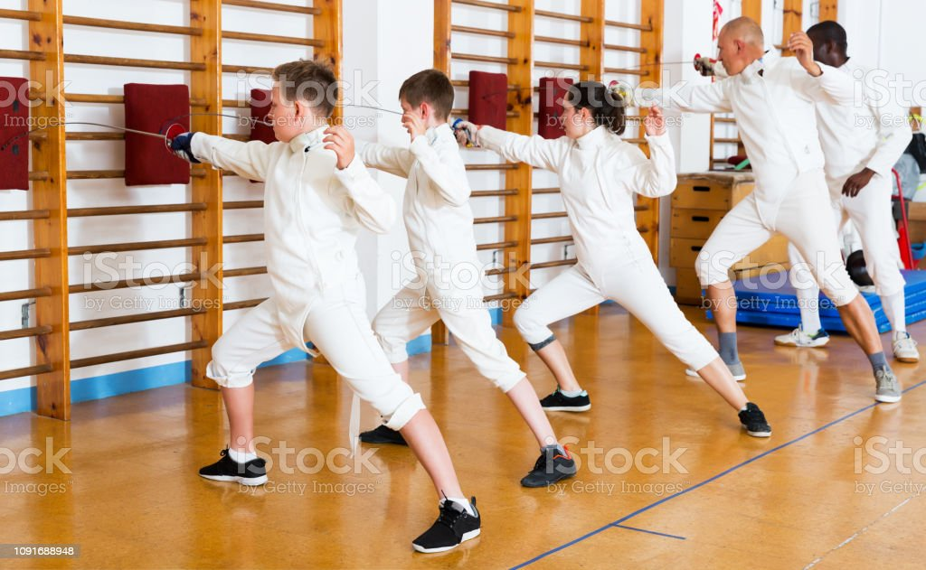 Group Practicing Fencing Techniques In Gym Stock Photo