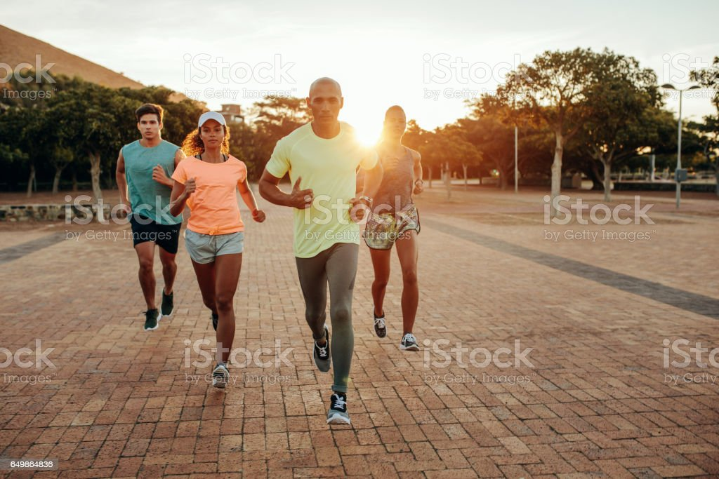 Group running outdoors in evening stock photo