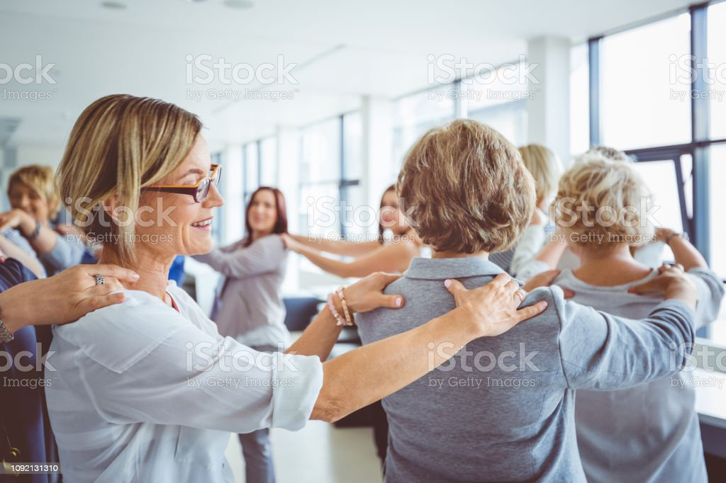 Group therapy for women Woman attending the training programme for businesswomen. Group of women walking in circle with their hands on shoulders. Adult Stock Photo