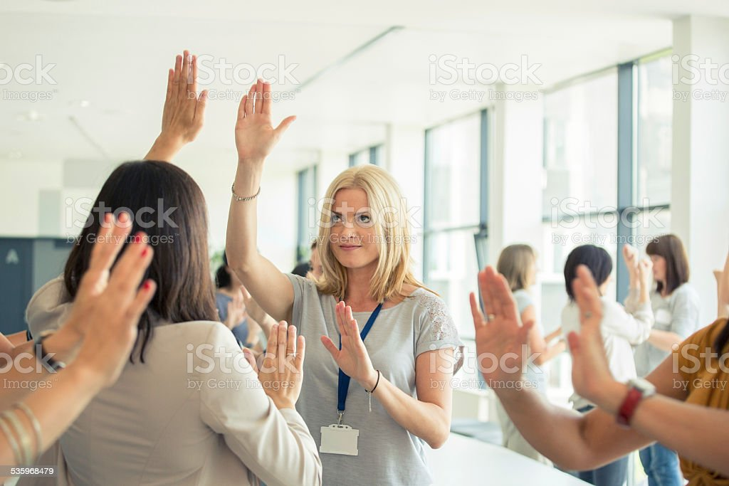 Group therapy for women Large group of women attending a training, playing with hands together. 2015 Stock Photo