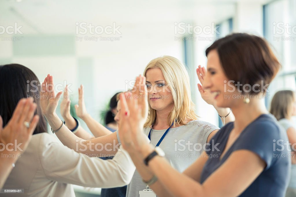 Group therapy for women Group of women attending a training, playing with hands together. 2015 Stock Photo