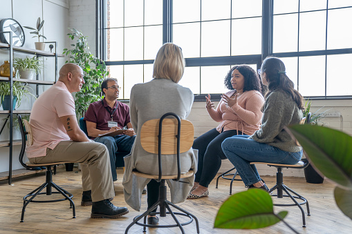 Multiethnic group of adults gather to discuss their mental health, addictions, and struggles in a group setting with a professional leading the discussion.