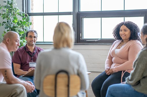 A group of five middle aged adults sit in a circle in attendance to a therapy session in urban office space.