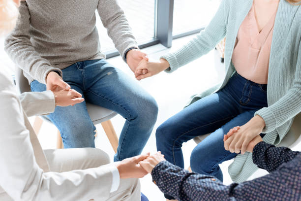 group therapy session partial view of people holding hands during group therapy session group therapy stock pictures, royalty-free photos & images