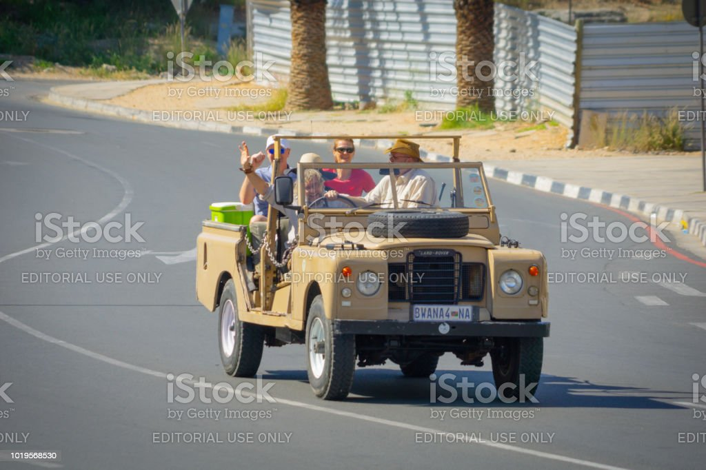 Group tourists being driven through city in open 4wd with guide. stock photo