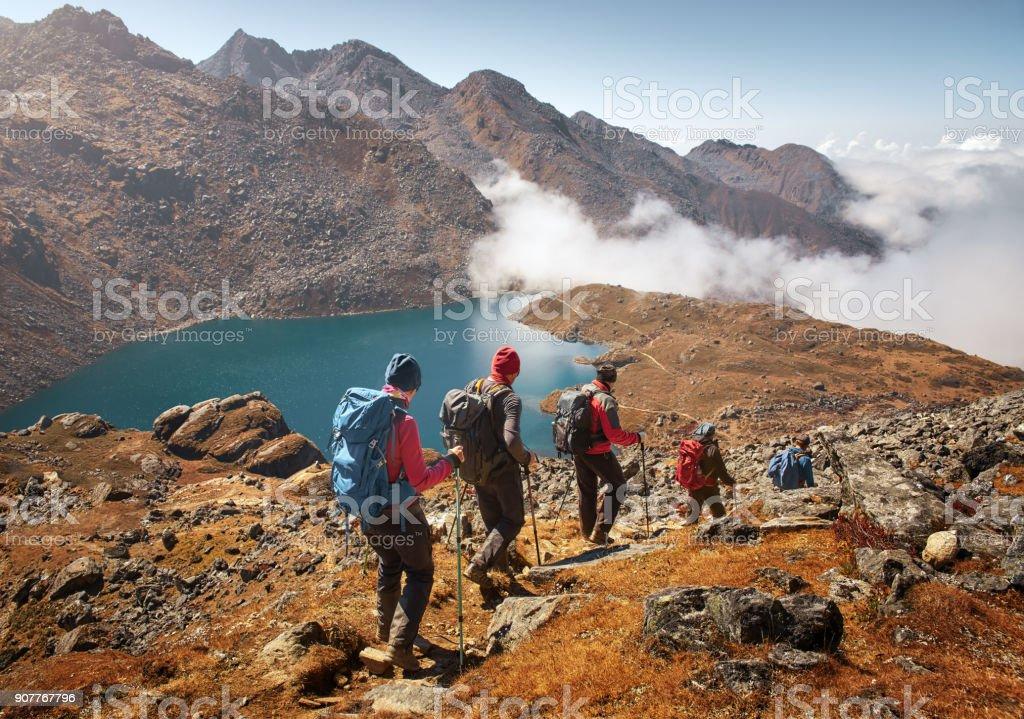 Touristes de groupe avec des sacs à dos descend vers le bas sur sentier de montagne au cours de la randonnée. photo libre de droits