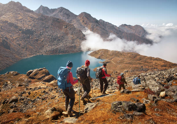 Group tourists with Backpacks descends down on Mountain Trail during Hike. stock photo