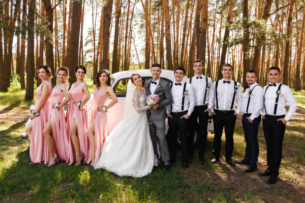 Group wedding photography. Bride and groom near wedding guests, bridesmaids in pink dresses and groomsmen with bow ties and suspender. Stylish and elegant wedding stock photo