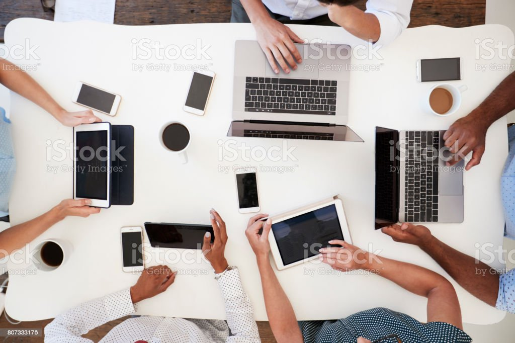 Group working at on computers with phones, overhead shot - foto stock