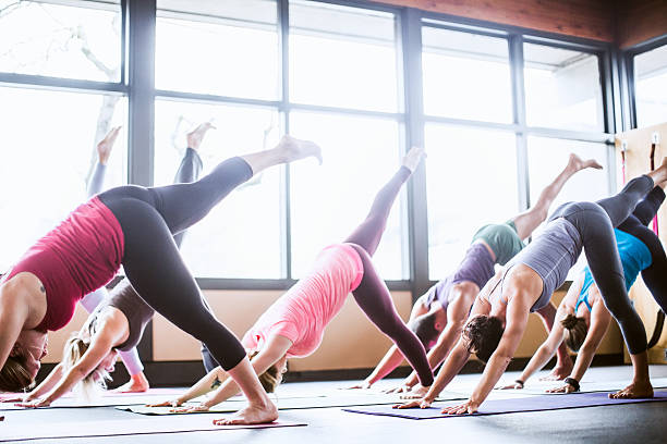 Group Yoga Class in Studio A mixed ethnicity group of men and woman practice different yoga forms and positions in a bright well lit studio.  They are in the one legged downward dog position ( Eka Pada Adho Mukha Svanasana ) yoga class stock pictures, royalty-free photos & images