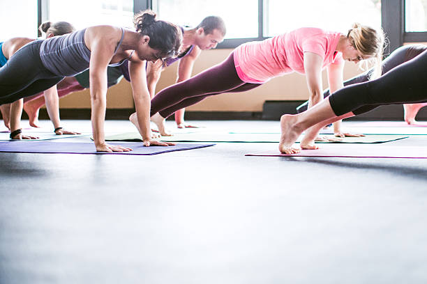 Group Yoga Class in Studio A mixed ethnicity group of men and woman practice different yoga forms and positions in a bright well lit studio.  Here they are in plank pose, or Uttihita Chaturanga Dandasana.  Horizontal with copy space. yoga class stock pictures, royalty-free photos & images