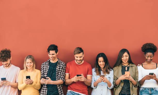 grupa młodych ludzi korzystających z mobilnego smartfona na zewnątrz - pokolenie milenialsów bawi się nowymi trendami aplikacje mediów społecznościowych - technologia młodzieżowa uzależniona - czerwone tło - kultura młodości zdjęcia i obrazy z banku zdjęć