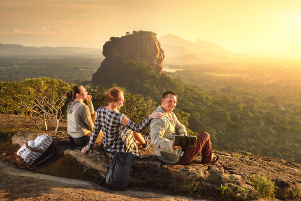 Group young tourists relaxes and watches during vacation colorful sunset on background of famous rocky plateau Lion peak, Sigiriya. Sri Lanka stock photo
