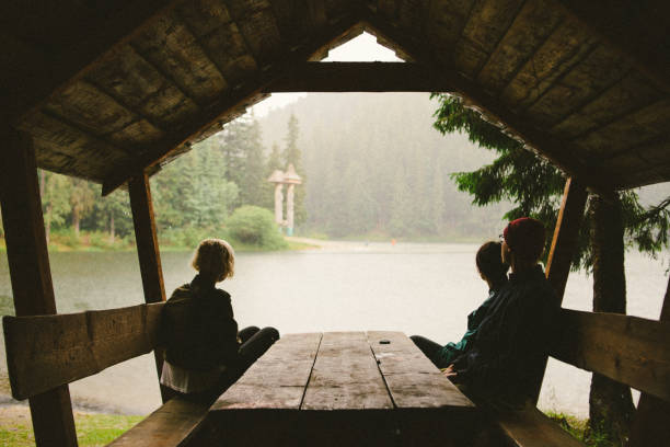 Groupe of friends in the forest Groupe of friends sitting at rainy summer day near the lake sheltering stock pictures, royalty-free photos & images