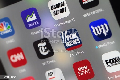 A grouping of popular News mobile apps on an iPad screen. Apps include major news outlets such a CNN, NY Times, Washington Post, Fox News, CNBC, Associated Press, Bloomberg News, Buzz Feed and several others.  Apps include both mainstream news, cable news, and financial news sites.  Selective focus on the center apps.