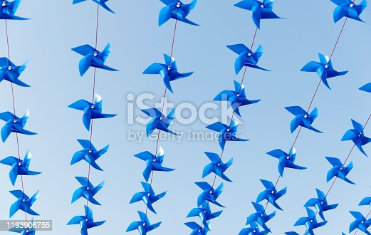 Groups of pinwheels hanging in a row.