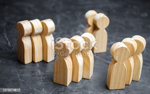 istock Groups of wooden people. The concept of market segmentation. Marketing segmentation, target audience, customer care. Market group of buyers. Customer analysis and customer relationship management 1073074612