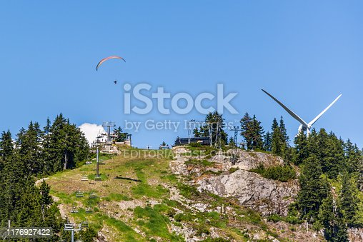Vancouver, British Columbia / Canada - 06/15/2015 Grouse Mountain chair lift, windmill and wood carvings are some of the sights here