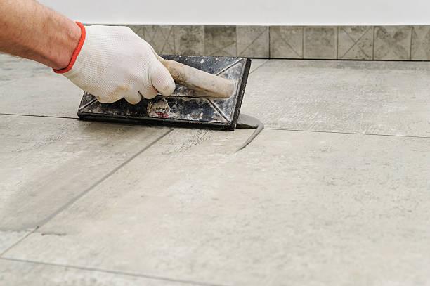 grouting ceramic tiles. - keramik fliesen handwerk stock-fotos und bilder