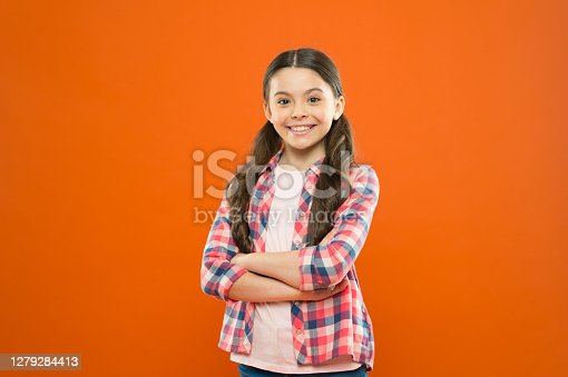 istock Grow mentally and physically healthy child. Child care and psychology. Wellbeing and health. Upbringing versatile personality. Childhood concept. Girl child stand orange background. Happy childhood 1279284413