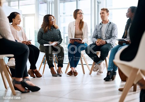 Shot of a group of businesspeople sitting in a circle and having a meeting in a modern office