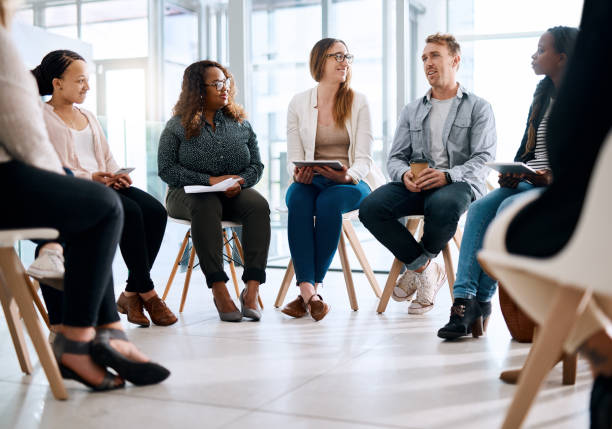 Grow your network, grow your career Shot of a group of businesspeople sitting in a circle and having a meeting in a modern office group therapy stock pictures, royalty-free photos & images