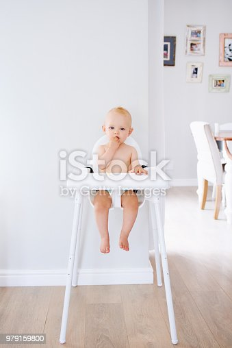 Portrait of an adorable baby girl sitting in a high chair at home and eating a snack