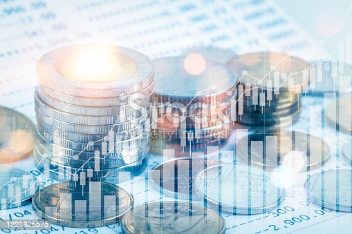 863469700 istock photo Growing money saving and investment concept; double exposure of coins stack on bank account book with growing trend candle stick graph; blue tone 1221625575