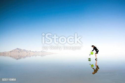 Young businesswoman watering a plant in vast open space with natural reflection.