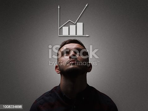 Growing schedule concept. Close up portrait of a man which looks up on growing schedule overhead. Grey background, copy space.