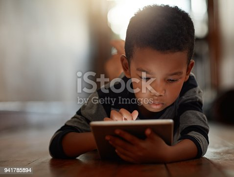 Shot of a young boy using his digital tablet while lying on the floor at home