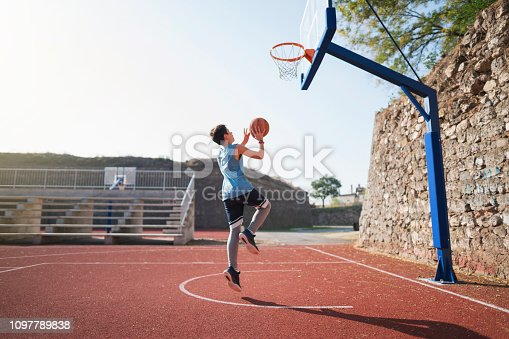 Teenage boy having a basketball training.