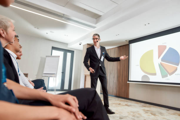 growing your business. full-length shot of young male speaker with headset in suit presenting a chart on the screen while giving a talk at business meeting, economic forum - theatre full of people stage foto e immagini stock