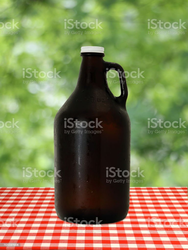 Growler at on Red Checkered Tablecloth against Blurry Trees stock photo