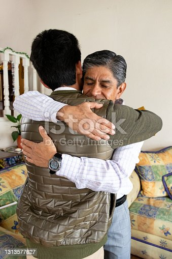 istock grown man hugging his son while smiling and closing his eyes 1313577627