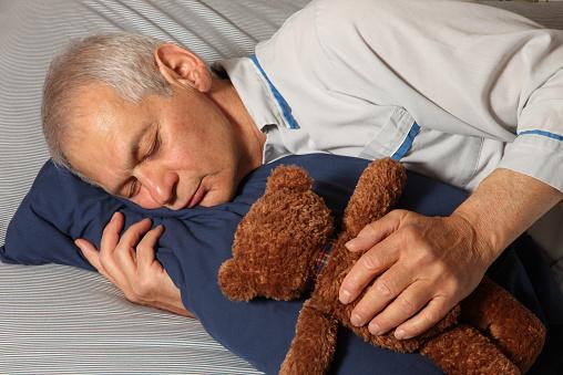 Grown man in deep sleep in bed with Teddy Bear