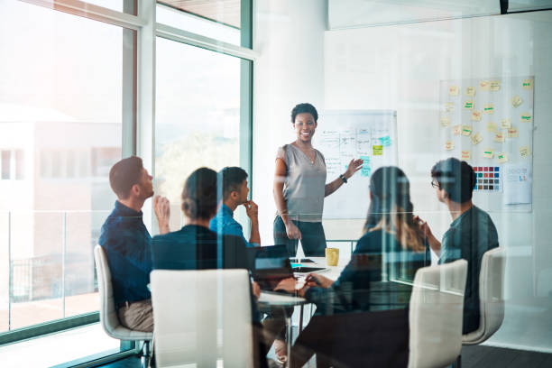 Growth creates more growth Shot of a group of businesspeople having a meeting in a modern office plan document stock pictures, royalty-free photos & images