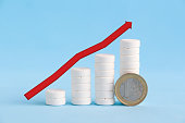 istock Growth graph made of stacked white pills and one euro coin 1212489956