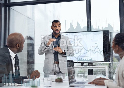 Shot of a young businessman delivering a presentation to his colleagues in the boardroom with cgi graphs superimposed against them