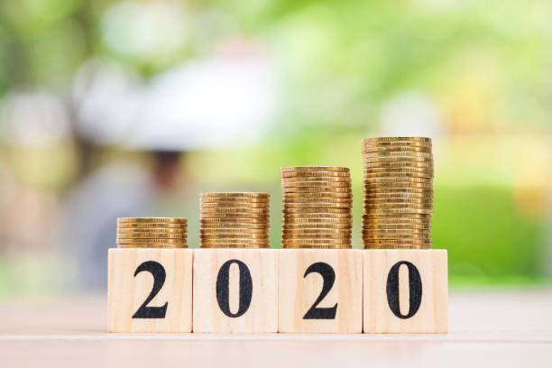 Growth of coins stack and wood blocks number 2020. Growth of coins stack on wood blocks number 2020. 2020 NEW YEAR Business and saving money concept. modern period stock pictures, royalty-free photos & images