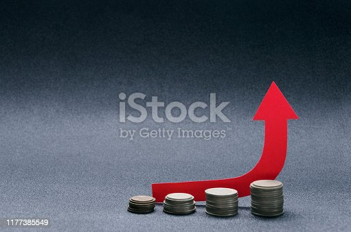 istock Growth red arrow and stacks of coins on the black surface.Empty space for text 1177385549