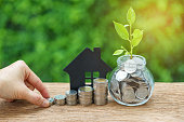 istock growth sprout plant in jar with full of coins and hand holding stack of coins with paper house as property or mortgage investment concept 834604862