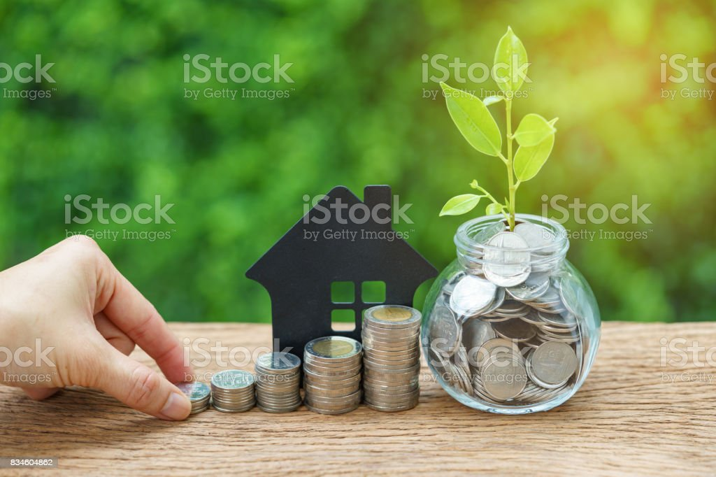 growth sprout plant in jar with full of coins and hand holding stack of coins with paper house as property or mortgage investment concept stock photo