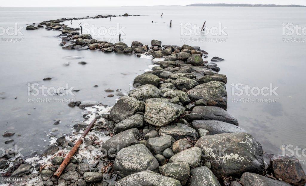 Groyne vågbrytare bålverk av stenar bildbanksfoto