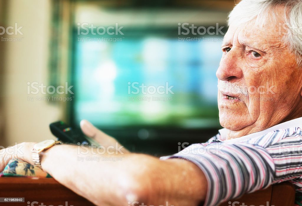 Grumpy 90-yer-old man disturbed while watching TV stock photo
