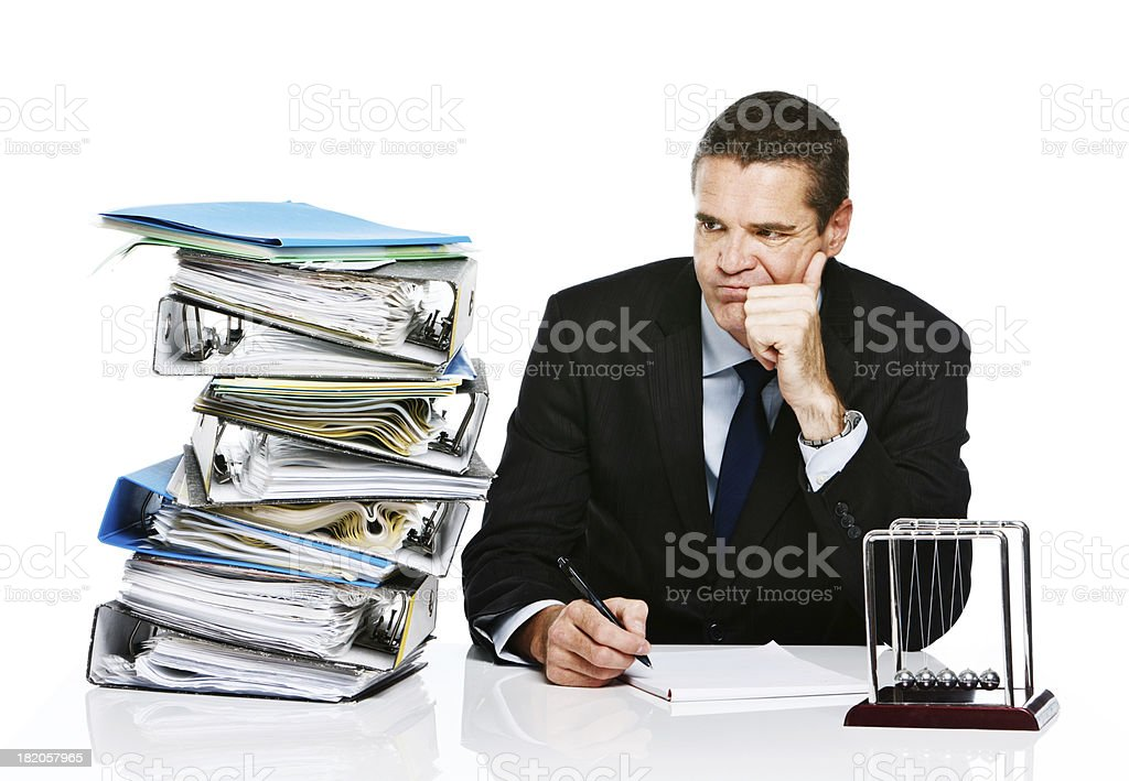 Grumpy businessman eyes enormous stack of work unhappily royalty-free stock photo